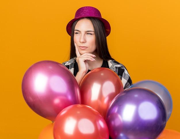 Mulher jovem e bonita suspeita com chapéu de festa em pé atrás de balões, colocando a mão na bochecha isolada em uma parede laranja
