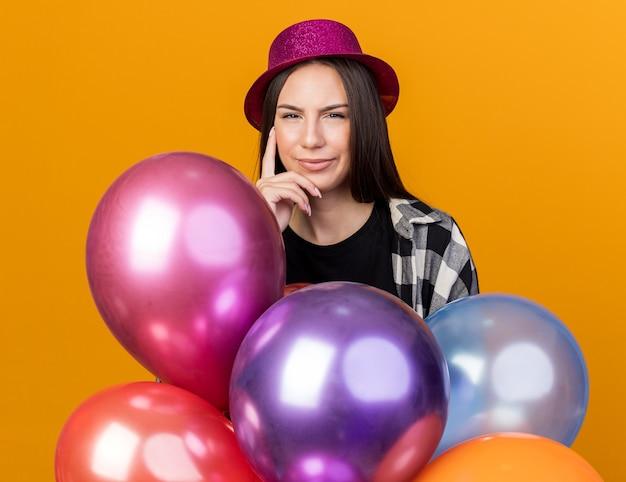 Mulher jovem e bonita suspeita com chapéu de festa em pé atrás de balões, colocando o dedo na bochecha isolada em uma parede laranja