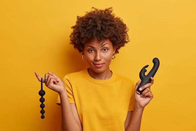 Mulher jovem e bonita tem experiência sexual com acessórios de brinquedos sexuais, segura contas anais para estimular a zona erógena em seu ânus, vibrador para atingir o orgasmo, fica de pé contra uma parede amarela vívida