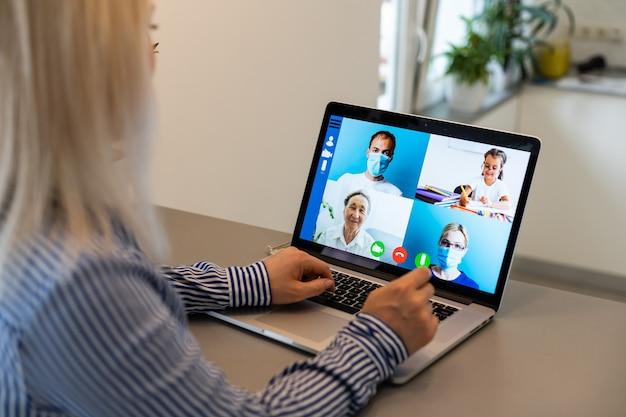 Mulher jovem e bonita tendo uma chamada de videoconferência através do computador. chame a reunião. escritório em casa. fique em casa e trabalhe em casa durante a pandemia de coronavirus