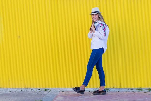 Mulher jovem e bonita tirando uma foto com e velha câmera vintage parede amarela