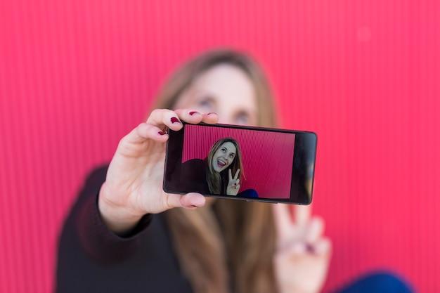 Mulher jovem e bonita tirando uma foto com um smartphone na parede vermelha