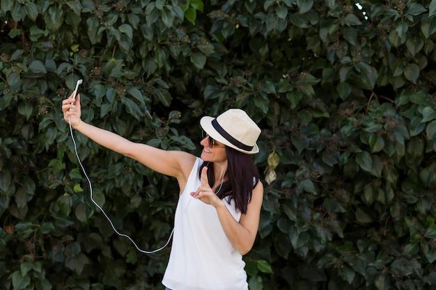 Mulher jovem e bonita tirando uma foto com um telefone inteligente. se divertindo conceito. ela está usando chapéu e óculos escuros.