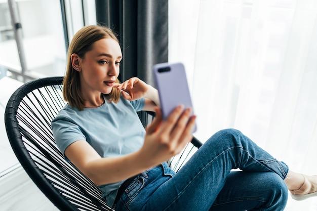 Mulher jovem e bonita tirando uma selfie perto da janela com cortinas em casa
