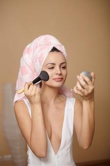 Mulher jovem e bonita toalha na cabeça, aplicar maquiagem no espelho