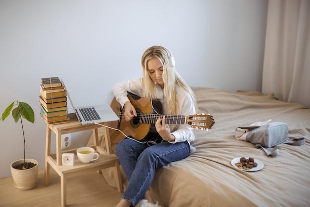 Mulher jovem e bonita tocando guitarra enquanto está sentado na cama em casa. linda garota com roupas casuais