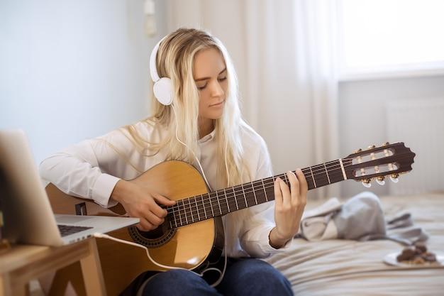 Mulher jovem e bonita tocando guitarra enquanto está sentado na cama em casa. retrato de uma linda garota em