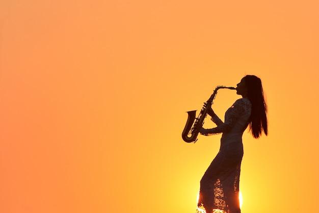 Mulher jovem e bonita tocando saxofone durante o pôr do sol, tailândia