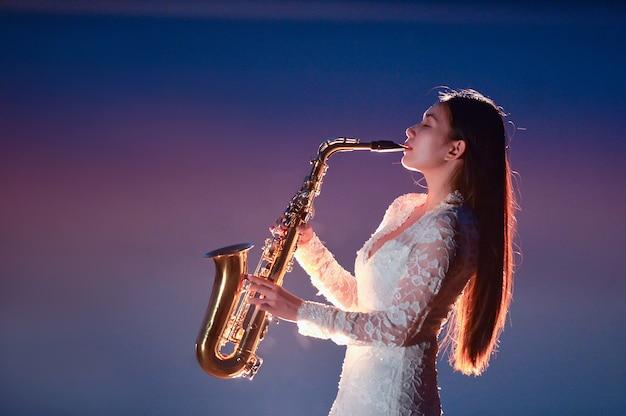 Mulher jovem e bonita tocando saxofone na hora azul após o pôr do sol, povo da tailândia, menina da tailândia, músico sexofone