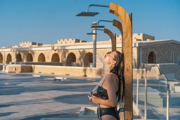 Mulher jovem e bonita toma um banho relaxante em um maiô em um dia ensolarado ao ar livre à beira-mar.
