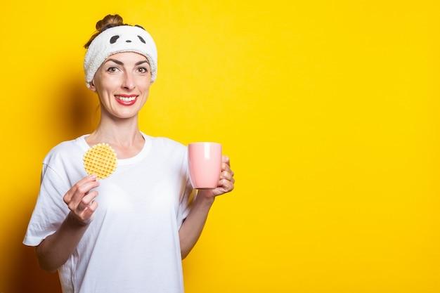 Mulher jovem e bonita tomando café com waffle belga em um fundo amarelo