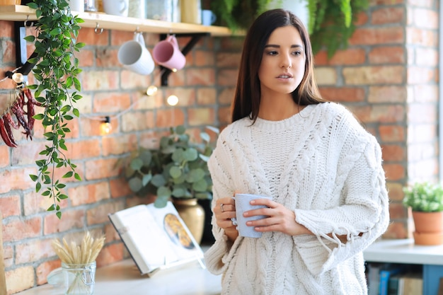 Mulher jovem e bonita tomando café ou chá na cozinha
