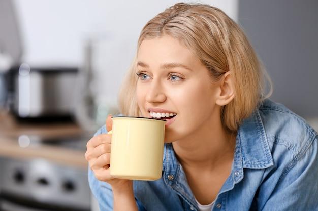 Mulher jovem e bonita tomando chá em casa