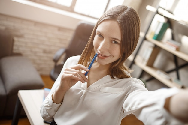 Mulher jovem e bonita tomando selfie na sala durante as férias. ela posa e sorri.