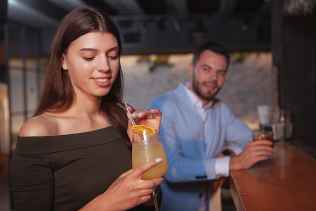 Mulher jovem e bonita tomando uma bebida no bar, homem bonito, sorrindo para ela sedutoramente
