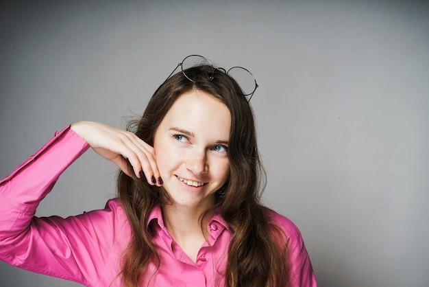 Mulher jovem e bonita, trabalhadora de escritório com uma camisa rosa e óculos, pensa em algo e sorri