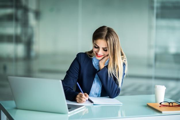 Mulher jovem e bonita trabalhando com um laptop e fazendo anotações em uma área de trabalho no escritório