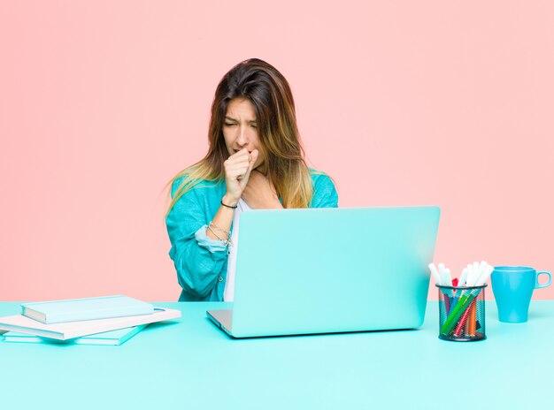 Mulher jovem e bonita trabalhando com um laptop, sentindo-se doente com sintomas de dor de garganta e gripe, tosse com a boca coberta