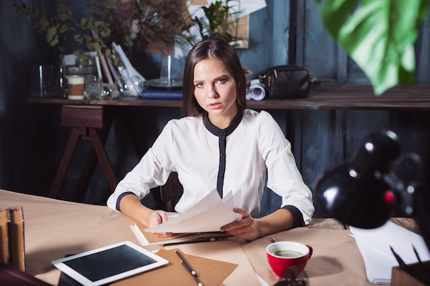 Mulher jovem e bonita trabalhando com uma xícara de café e um notebook no escritório.