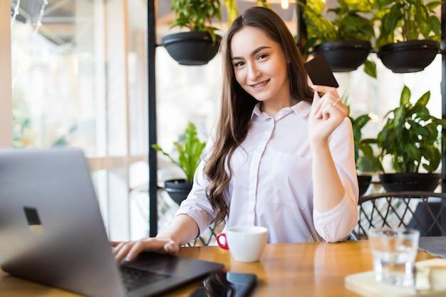 Mulher jovem e bonita trabalhando em um café em um laptop segurando um cartão de crédito para pagamento