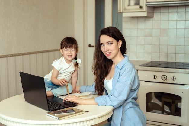 Mulher jovem e bonita trabalhando em um escritório em casa, sentado em uma mesa na cozinha com um laptop. ao lado dela está sua filhinha. eles estão sorrindo alegremente