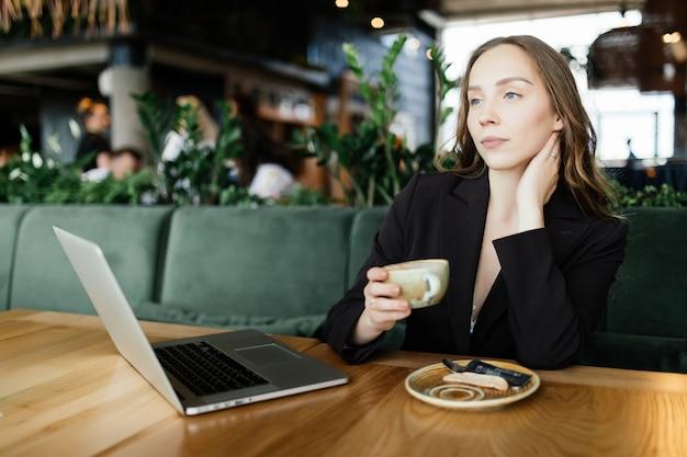 Mulher jovem e bonita trabalhando em um laptop em uma cafeteria