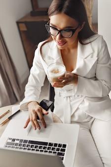 Mulher jovem e bonita trabalhando em um laptop enquanto está sentado na sala, bebendo café