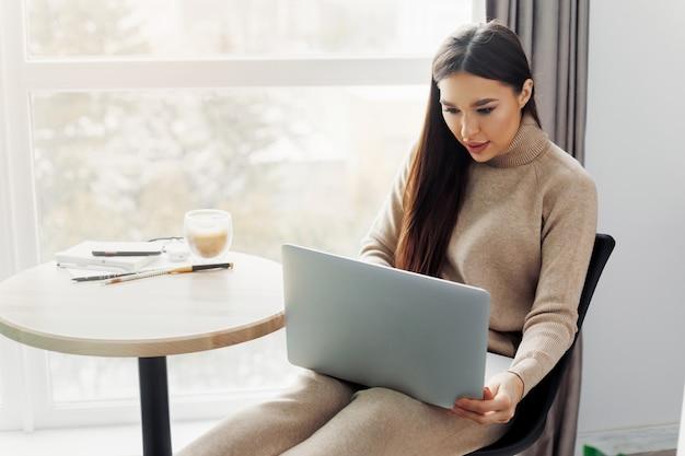 Mulher jovem e bonita trabalhando no computador laptop enquanto está sentado na sala de estar, bebendo café. escritório doméstico durante a quarentena do coronavirus ou covid-19. comunica-se na internet.
