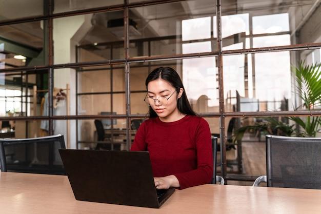 Mulher jovem e bonita trabalhando no escritório no laptop.