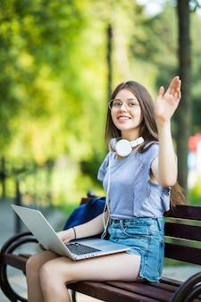 Mulher jovem e bonita trabalhando no parque e acenando olá no parque