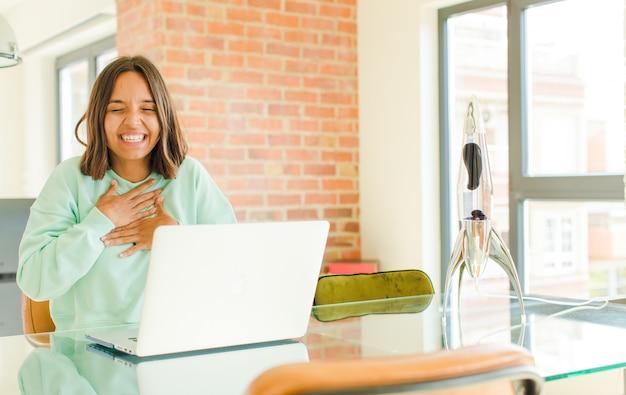 Mulher jovem e bonita trabalhando, rindo alto de alguma piada hilária, sentindo-se feliz e alegre, se divertindo