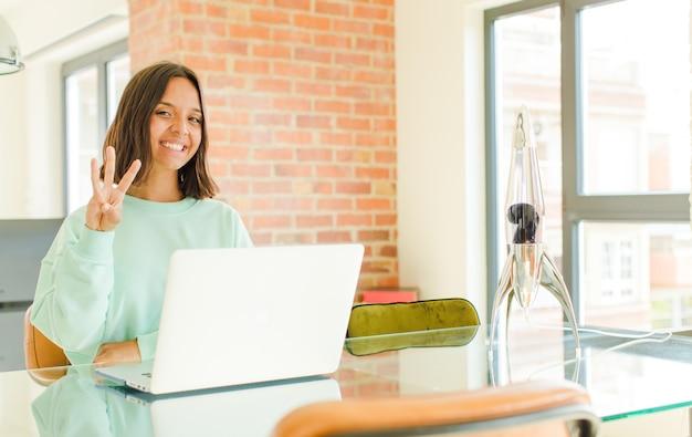 Mulher jovem e bonita trabalhando, sorrindo e parecendo amigável, mostrando o número um ou primeiro com a mão para a frente, em contagem regressiva