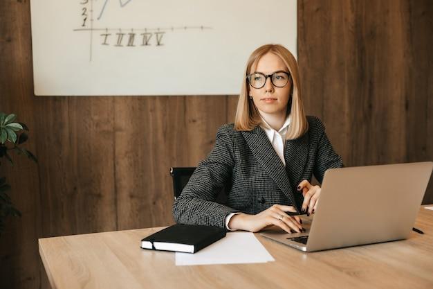 Mulher jovem e bonita trabalhando usando o computador laptop, olhando pela janela distraidamente, bom trabalhador de escritório responsável.