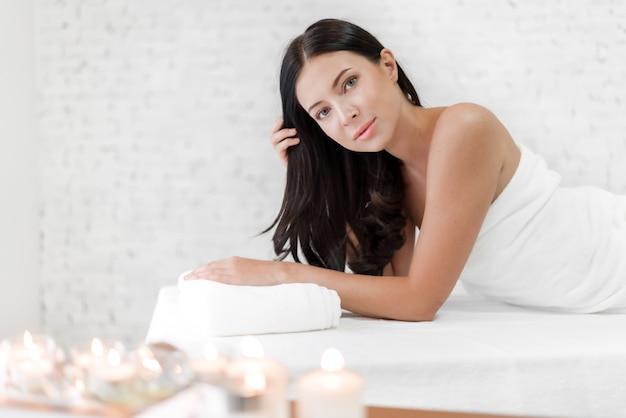 Mulher jovem e bonita tratamento de pele de beleza relaxante deitada na toalha em salão de massagens e spa