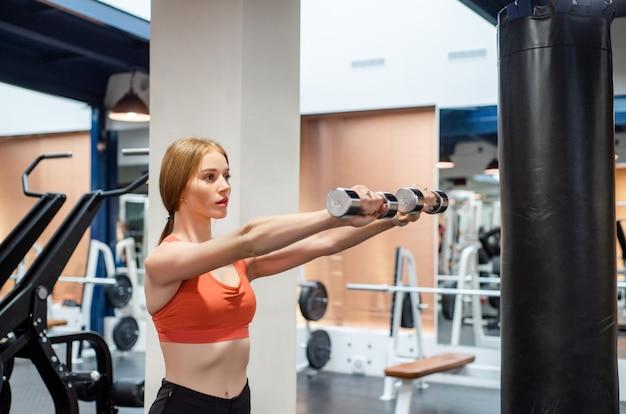 Mulher jovem e bonita treina deltóide na academia com halteres