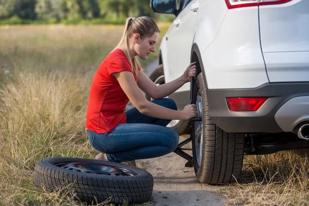 Mulher jovem e bonita trocando um pneu furado no campo