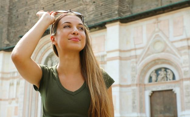 Mulher jovem e bonita turística na cidade medieval italiana de bolonha com a basílica de san petronio ao fundo.