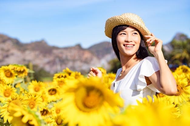 Mulher jovem e bonita usa chapéu de palha e relaxando em um campo de girassóis em um vestido branco.