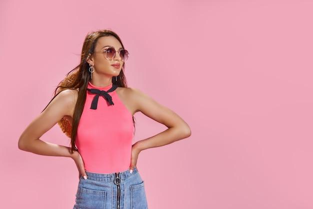 Mulher jovem e bonita usa óculos escuros e chapéu de palha no fundo rosa