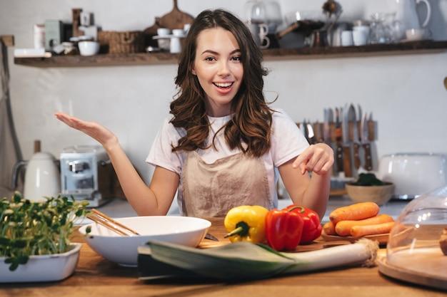 Mulher jovem e bonita usando avental cozinhando salada saudável na cozinha em casa, apontando