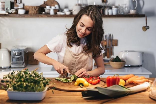 Mulher jovem e bonita usando avental cozinhando salada saudável na cozinha em casa, cortando vegetais