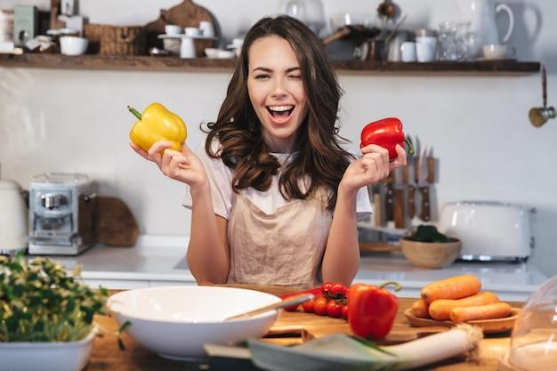Mulher jovem e bonita usando avental cozinhando salada saudável na cozinha em casa, segurando pimentão