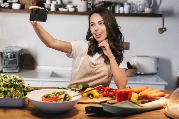 Mulher jovem e bonita usando avental cozinhando salada saudável na cozinha em casa, tirando uma selfie com o celular