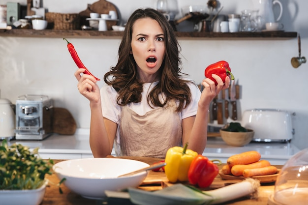 Mulher jovem e bonita usando avental cozinhando salada saudável na cozinha em casa