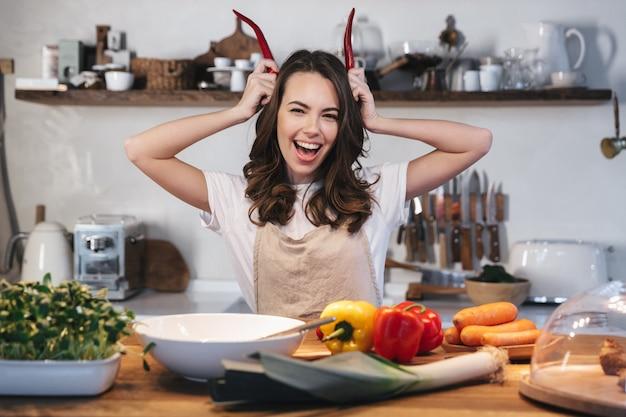 Mulher jovem e bonita usando avental cozinhando uma salada saudável na cozinha em casa, segurando pimenta malagueta