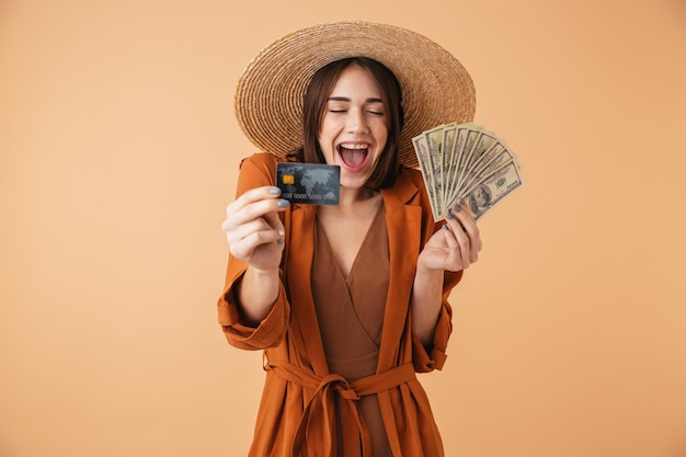 Mulher jovem e bonita usando chapéu de palha e roupa de verão em pé, isolada na parede bege, segurando um cartão de crédito palstic, mostrando notas de dinheiro