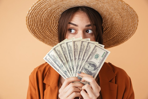 Mulher jovem e bonita usando chapéu de palha e roupa de verão em pé, isolada sobre uma parede bege, mostrando notas de dinheiro