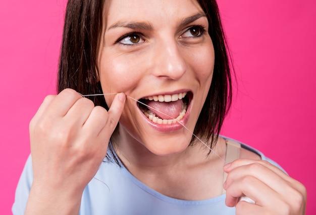 Mulher jovem e bonita usando fio dental em fundo rosa