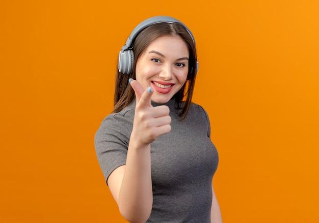 Mulher jovem e bonita usando fones de ouvido, ouvindo música isolada em laranja