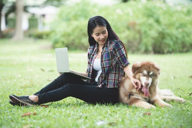 Mulher jovem e bonita usando laptop com seu cachorro pequeno em um parque ao ar livre. retrato do estilo de vida.
